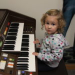 A little girl plays the piano in Music Therapy