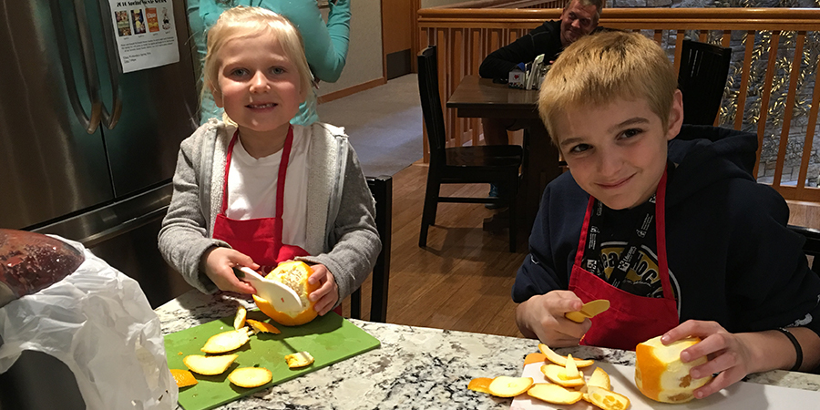 Two kids cutting oranges at a Kids Can Cook class