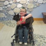 Boy in a wheelchair with a therapy dog
