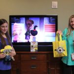 Girls with Minion toys watching a movie