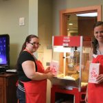 Two volunteers making popcorn for Movie Night