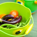 Eggplants, peas and other vegetables in a bucket