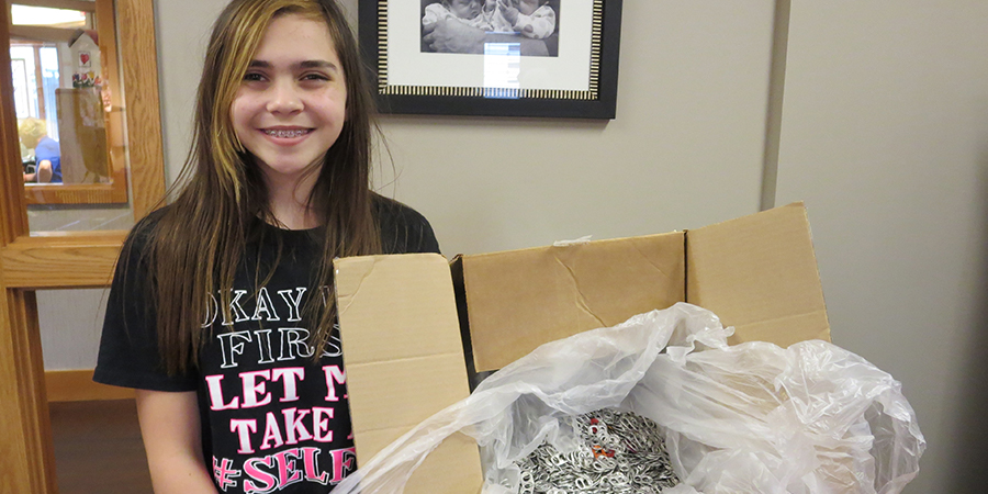 Girl poses with pop tabs she donated