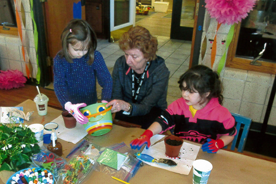 Girls planting seeds in Family Garden Education