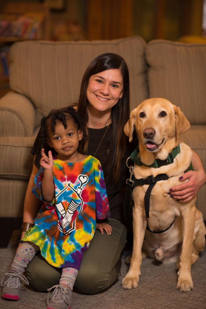Therapy dog Archie with his handler and a guest