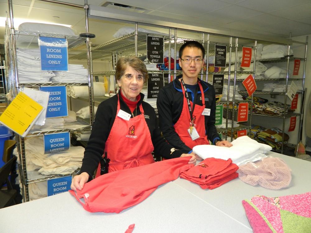 Volunteers in the Laundry Room folding clean linens